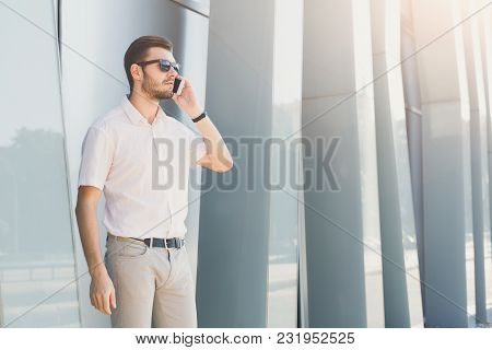 Attractive Thoughtful Businessman Or Lawyer In Sunglasses Is Talking On Cell Phone And Looking Away
