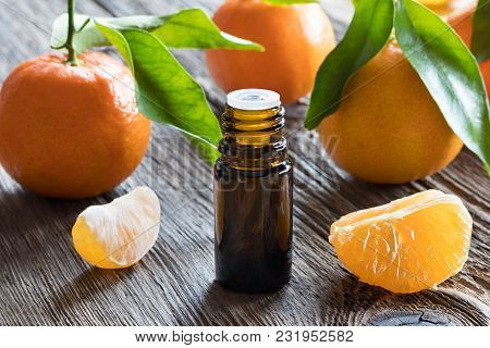 A Bottle Of Tangerine Essential Oil With Fresh Tangerines And Leaves