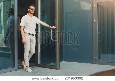 Confident Pensive Man Opening The Door And Walking Out From The Modern Office Building, Full Length,