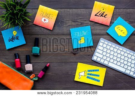 Beauty Blogging Concept. Work Desk With Keyboard, Cosmetics And Social Media Icons On Dark Wooden De
