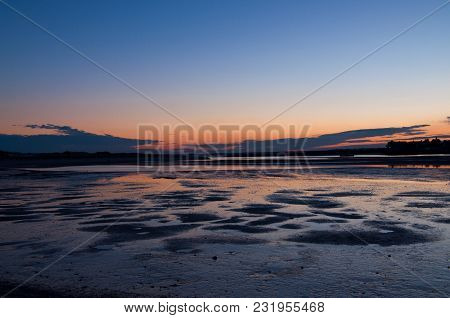 Sunset Colors Reflected In Tide Pools On The Beach
