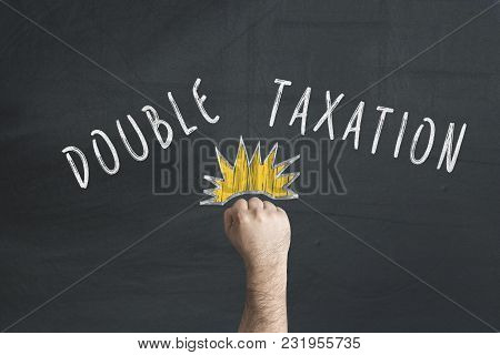 Financial Double Tax Concept With Punching Fist Against Blackboard.