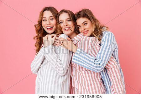 Three beautiful young girls 20s wearing colorful striped pyjamas hugging together and having fun during sleepover isolated over pink background