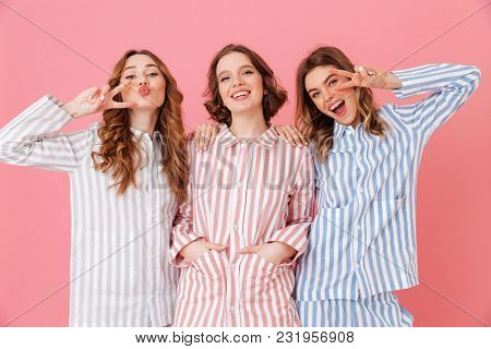Three cheerful women 20s wearing leisure clothings having fun at slumber party and showing peace signs isolated over pink background