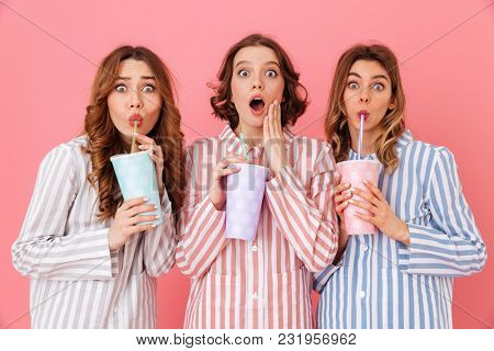 Three brunette girls 20s wearing leisure clothing drinking cold beverages from paper cups and expressing surprise during happy sleepover isolated over pink background