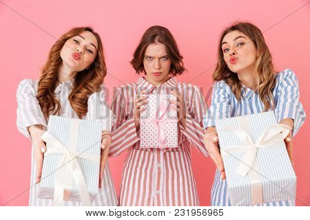 Photo of brunette girlfriends 20s in leisure wear holding and demonstrating present boxes at happy sleepover isolated over pink background