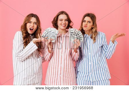 Photo of envious women 20s in colorful striped pajamas expressing irritation while lucky female friend holding lots of money dollar cash at home isolated over pink background