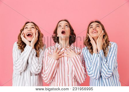 Portrait of three joyful young girls 20s wearing colorful striped pajamas looking upward on copyspace with excitement during sleepover isolated over pink background