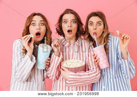 Three fascinating young girls 20s in colorful homewear eating pop corn during watching thrilling and exciting movie at home party isolated over pink background