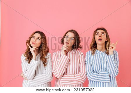 Portrait of three cute young girls 20s wearing colorful striped pyjamas posing on camera with pensive or brooding look during sleepover isolated over pink background
