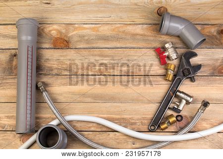 Fittings, Pipe, Valves, Plastic Pipe For Water, Adjustable Wrench On The Wooden Background. Top View