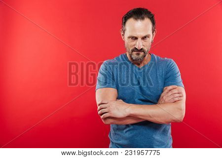 Photo of aggressive man wearing casual t-shirt standing with hands crossed and looking on camera with angry gaze isolated over red background