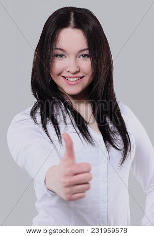 Successful business  woman posing against gray background.