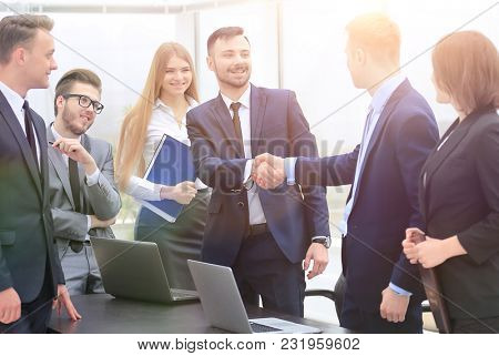representatives of the two business teams greet each other