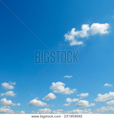 Small white clouds against the blue sky. Copy space