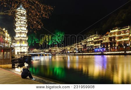 Fenghuang, China - January 26 2018 : A Girl Sit Beside The Shore Look For The Night At The Old Town