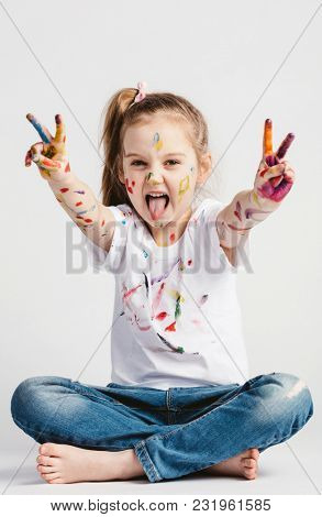 A girl showing victory sign with her hand, sticking her tounge out. Rebel kid.