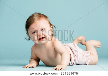 Crawling baby girl crying on the floor. Baby blue background. Sad kid.