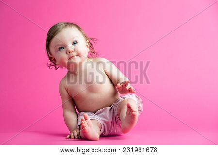 Little baby sitting, leaning over. Pink background. Funny sweet child. Losing balance.