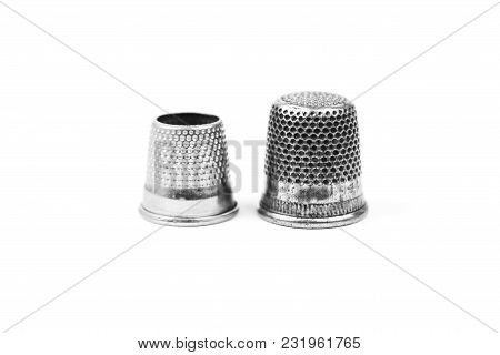 Two Metal Silver Sewing Thimbles On A White Background. Sewing Accessories And Tools