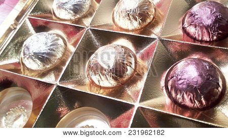 A Box Of Chocolates In Foil Close-up Blurred Background