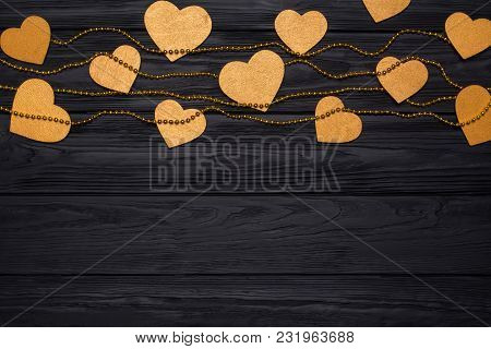 Flat Lay Border Of Golden Hearts And Beads. Festive Decor On A Black Wooden Background. View From Ab