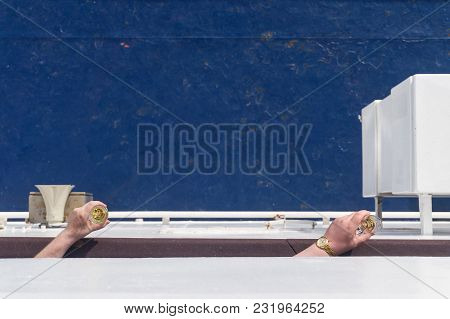Men's Hands Holding Glasses Of Wine On A Ship Deck