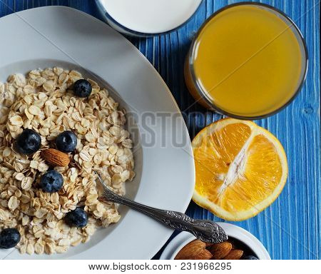Healthy eating, food and diet concept - tasty oatmeal with berries and glass of orange juice. Top view. Blue wooden background.