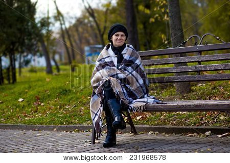 Attractive Middle Aged Woman Covered With Blanket Sit On Bench In Spring Day