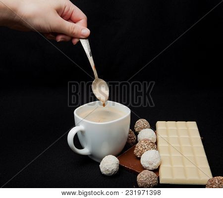 Woman Adding Sugar In Coffee In Cafe. Cofe, Stack Of Black And White Chocolate Isolated On Black Bac