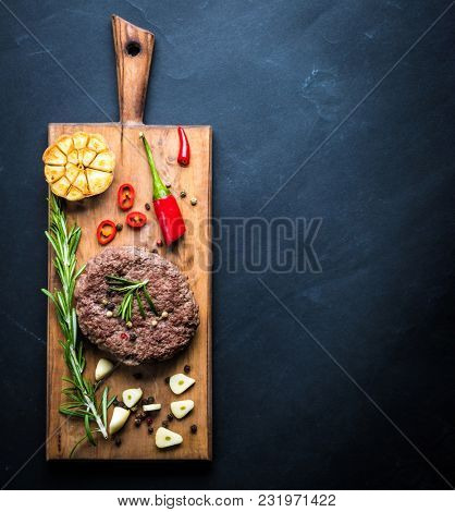 Delicious beef burger steak with spices and herbs on cutting board and slate background, top view