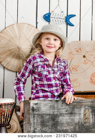 cute little girl in hat sitting in big old chest