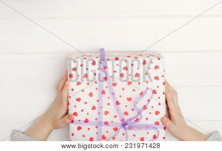 Little kid's hands holding gift box wrapped in heart patterned wrapping paper and bound with a neat purple bow and ribbon, top view