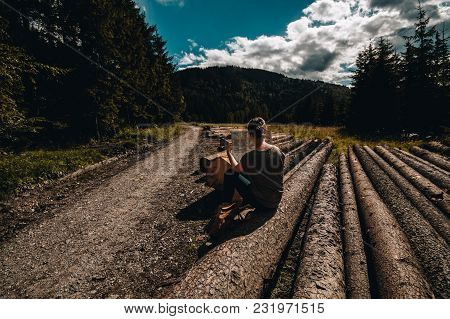 A Girl With A Map Sitting On A Wooden Log In Mountains