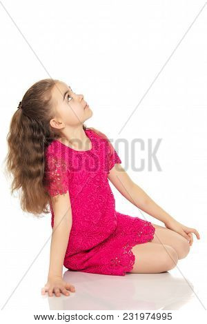 A Beautiful Little Girl Of Primary School Age, With Long Flowing Hair, In A Bright Red Dress.she Sat