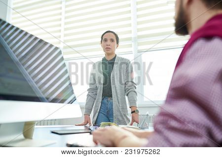 Low Angle View Of Caucasian Female Office Worker Talking To Her Male Colleague Sitting In Front Of C