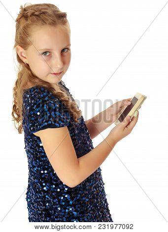 Beautiful Little Girl In A Festive, Glittering, Blue Dress, Holding A Mobile Phone . Turning Sideway