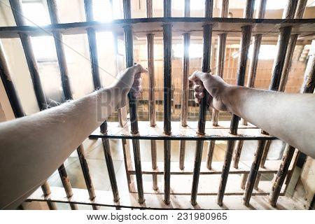 Prisoner Man In Jail Holding Hand In Prison Cell Grid