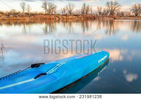 Fort Collins, CO, USA - March 17, 2018: Racing stand up paddleboard on a calm lake at dusk - 2018 model of All Star SUP by Starboard.