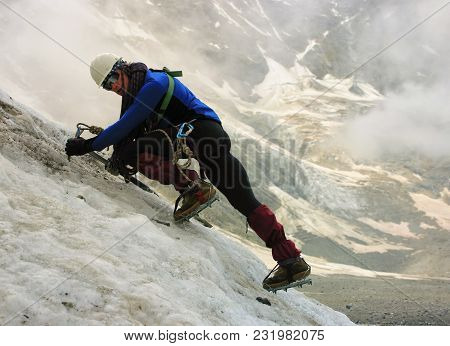 The Climber Climbs The Glacier. He Is Wearing Equipment. Helmet, Rope, Crampons And Ice Ax. On The B