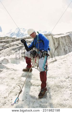 The Climber Sits On A Glacier, Stabbing An Ice Ax In The Ice. In The Background A Lot Of Ice, A Moun