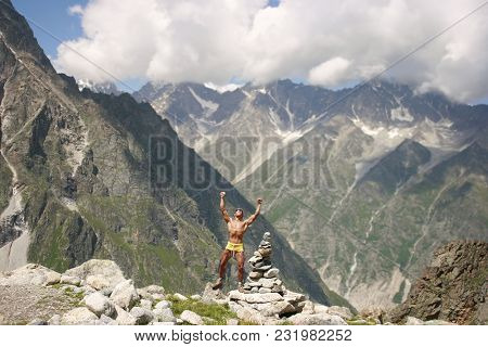 Athletic Man With A Sporting Body, A Climber, Stands With Rising Hands At Great Height In Front Of T