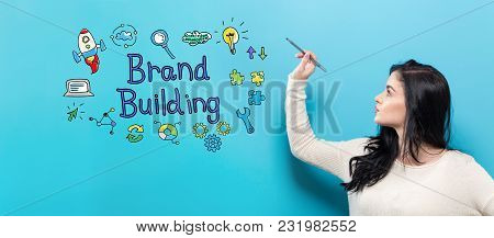 Brand Building With Young Woman Holding A Pen On A Blue Background