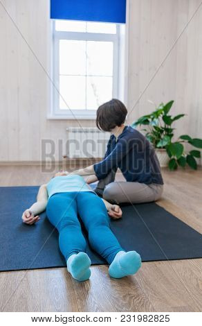 Woman Lying On Mat And Having Class Of Body-oriented Psychotherapy With Special Coach.