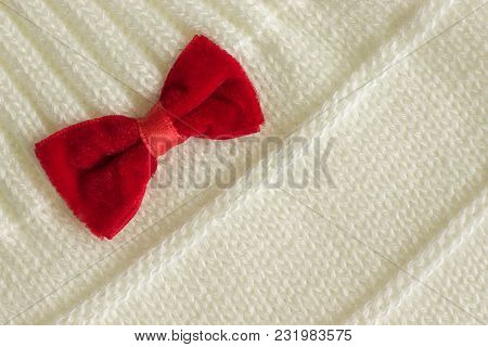 White Knitted Fabric With A Pattern And A Red Bow In The Corner, Background Or Texture