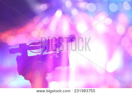 Professional Digital Video Camera In Concert Light On Stage With Colorful Background