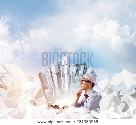 Young Man Writer In Hat And Eyeglasses Using Typing Machine While Sitting At The Table Among Flying