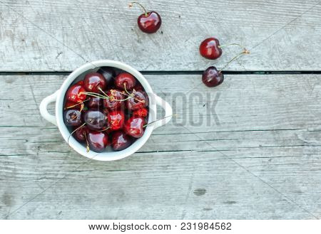 Fresh Garden Cherry In Bowl On Wooden Table. Top View With Copy Space