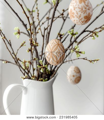 Easter eggs hanging on a spring blossom branch. Easter decorations. Easter background.