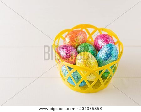Yellow Basket With Colorful Eggs On A White Rustic Table. Decorations For The Easter Table.